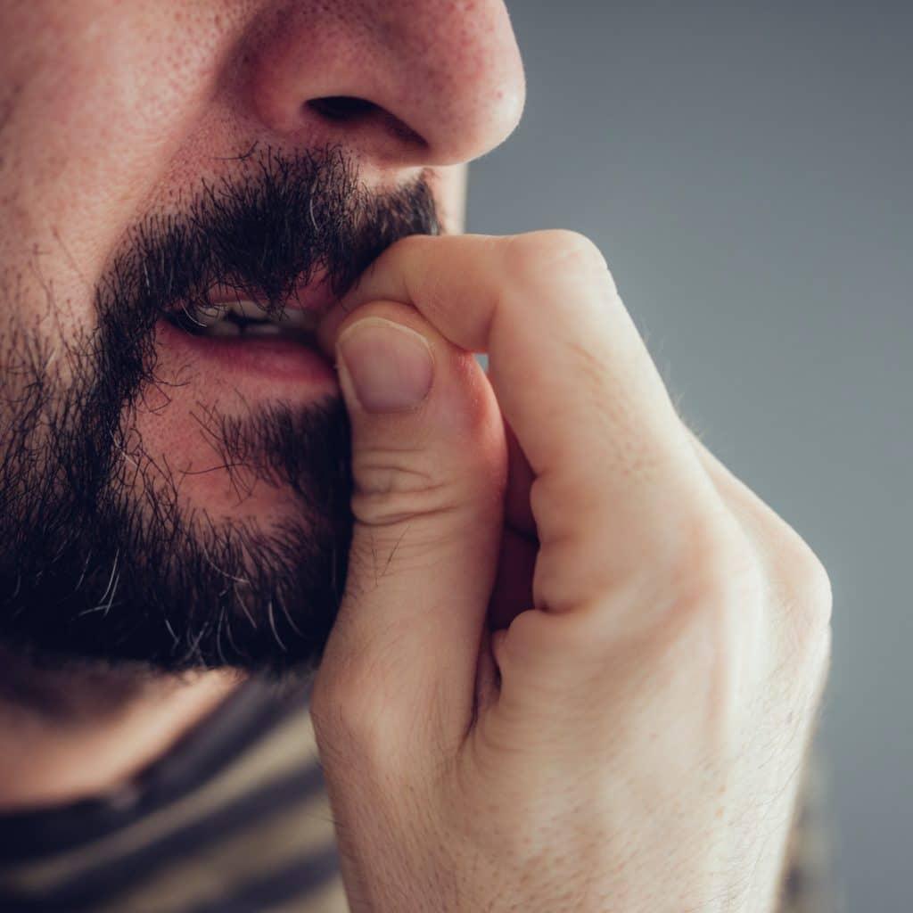 homme se ronge les ongles il a envie de craquer
