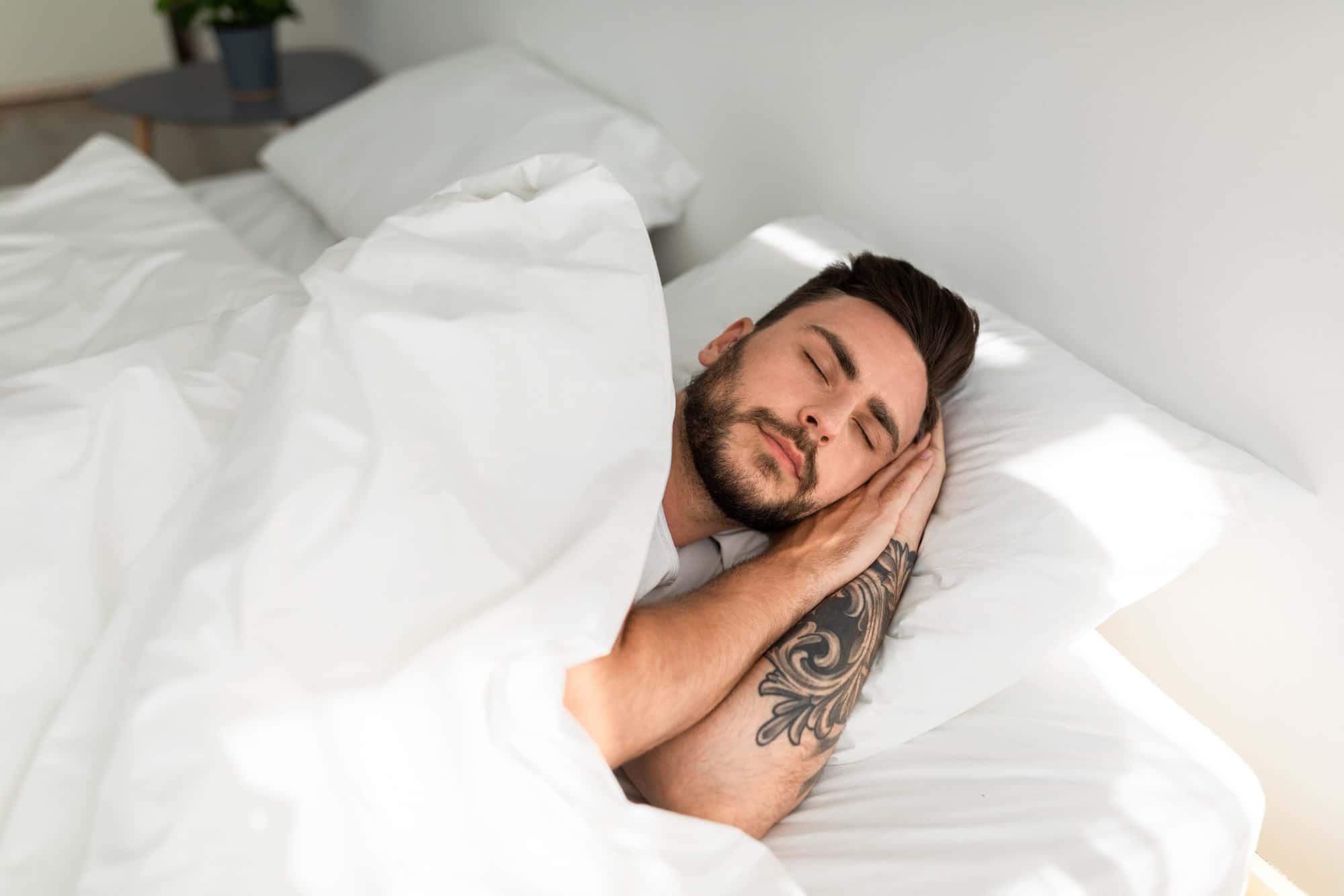 homme tatoué dort dans son lit