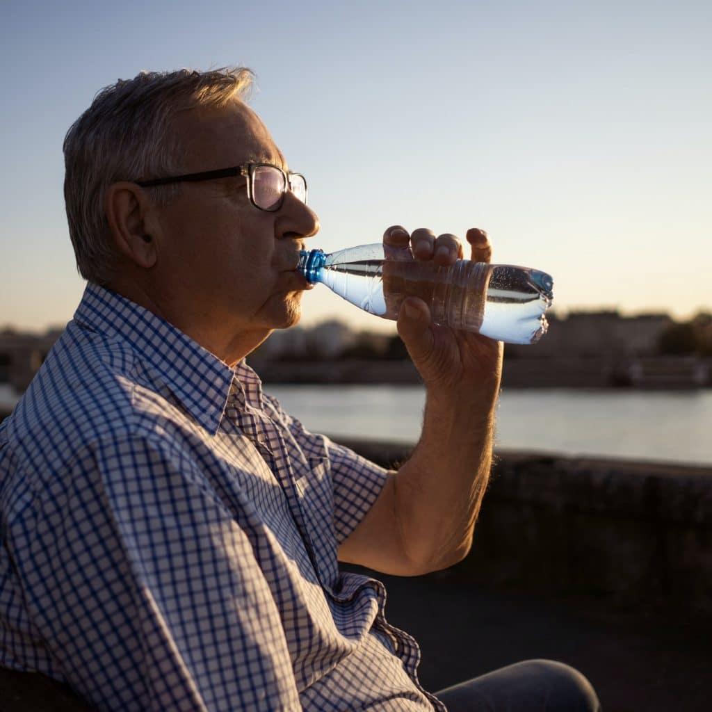 homme agé bois de l'eau dans une bouteille