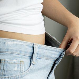 femme dans un pantalon trop grand après une perte de poids