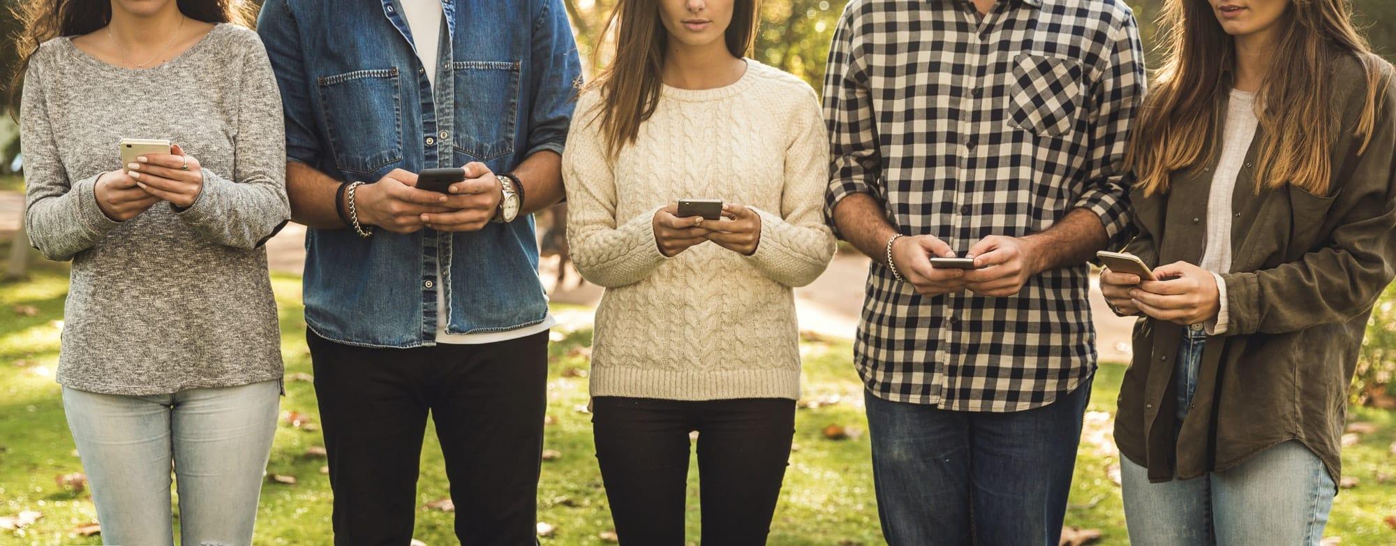 groupe d'amis regardent leurs téléphones