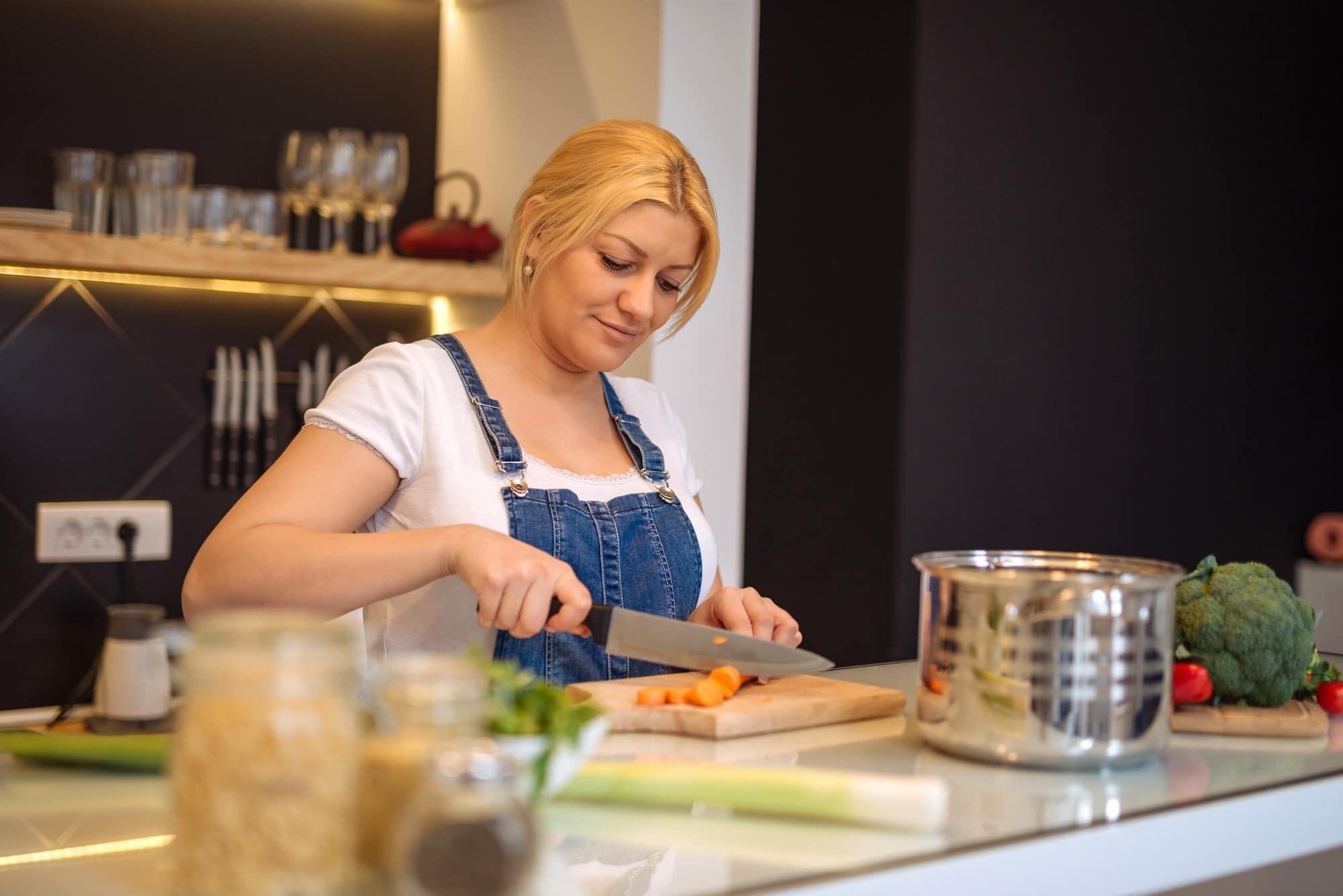 femme coupe une carotte et cuisine un repas sain et équilibré