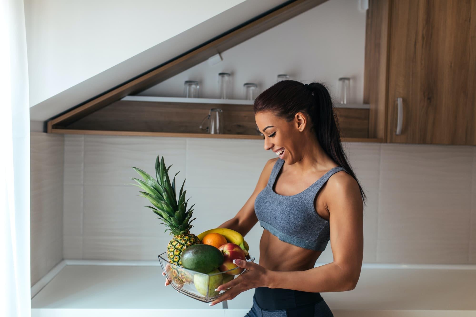 femme tient un saladier de fruits
