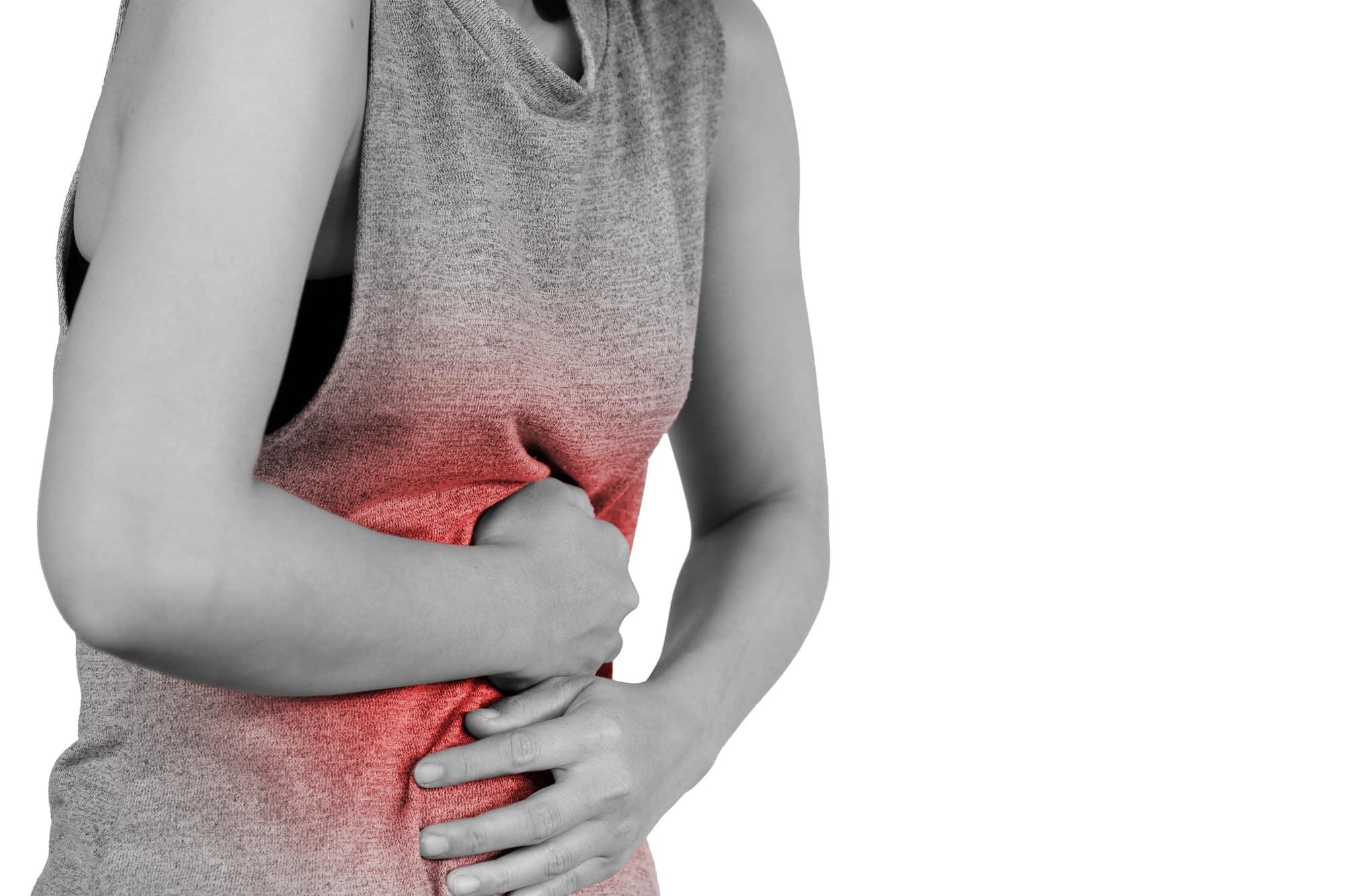 femme a mal au ventre photo en noir et blanc zone rouge au niveau de la douleur
