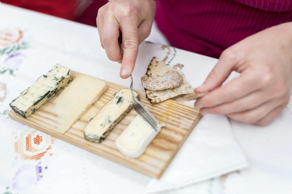 zoom sur des mains coupant du fromage