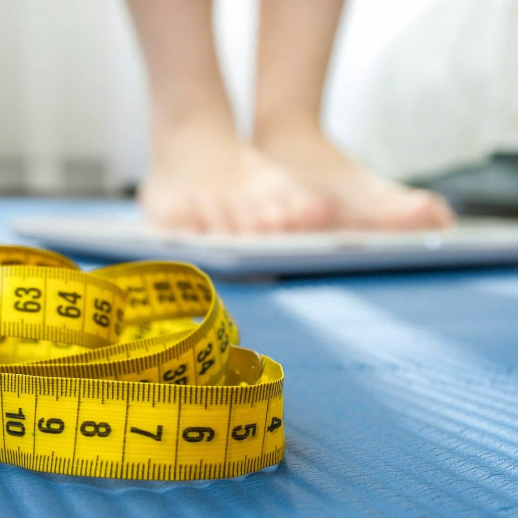 Measuring tape, fitness mat and young woman weighting on scales. Concept of dieting, sports, loosing