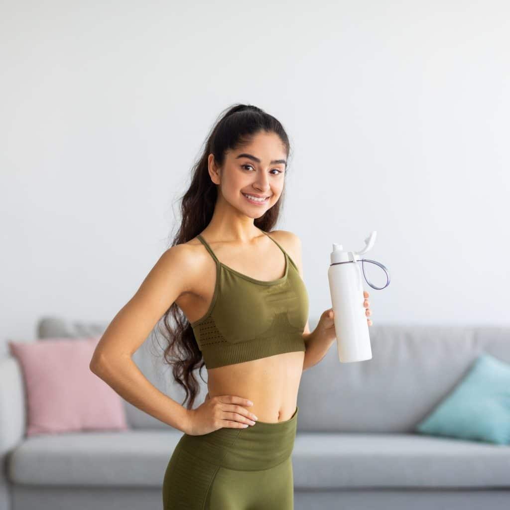 femme en vêtements de sport tient une gourde dans la main
