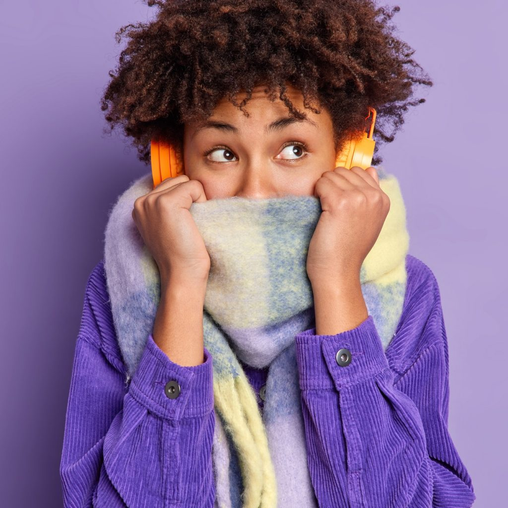 Chilly woman face buried in her scarf