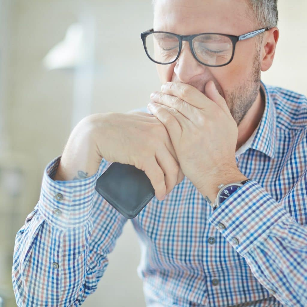 man with glasses tired and yawning