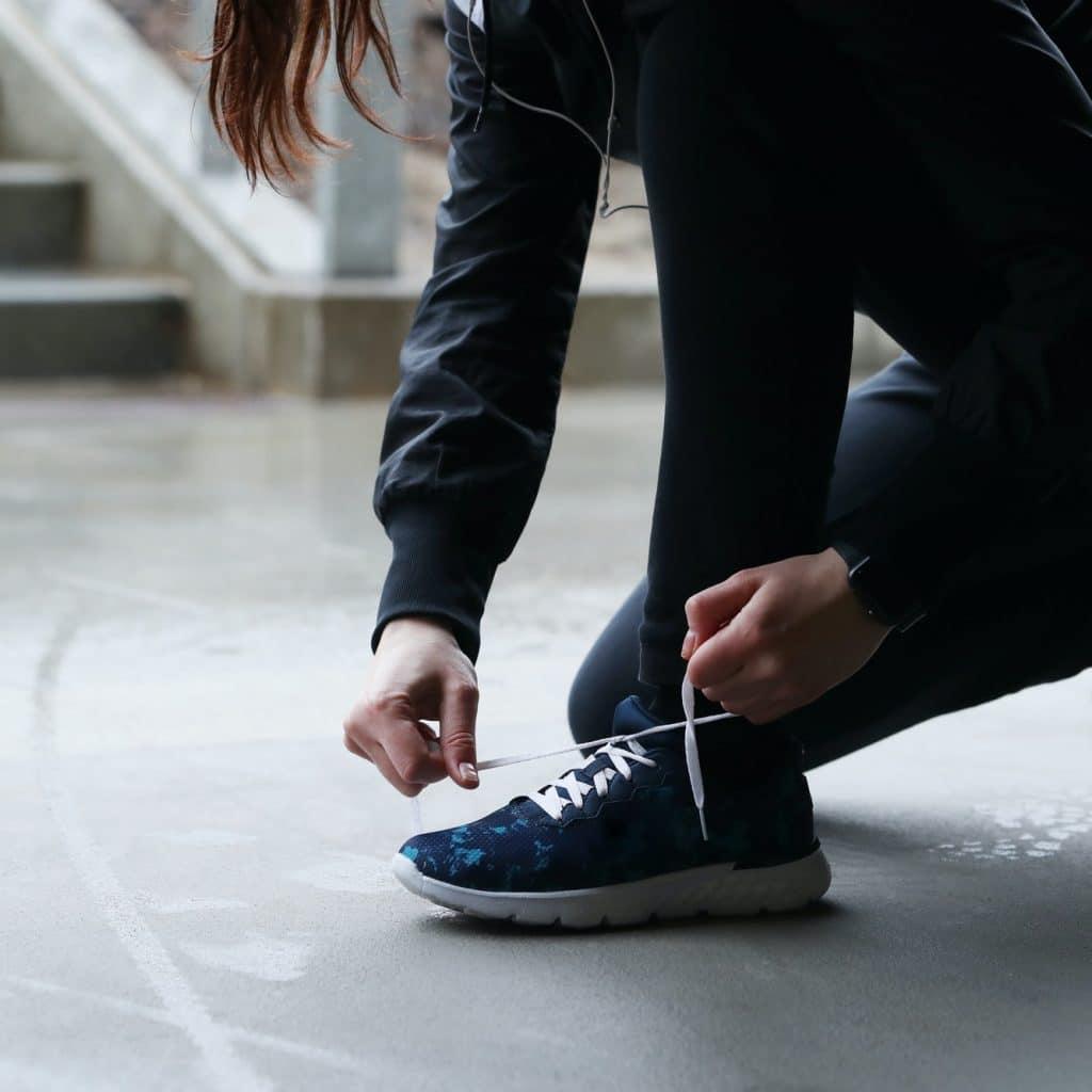 femme fait ses lacets pour aller faire du sport