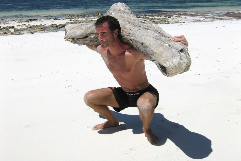 MovNat creator Erwan Le Corre squatting on the beach.