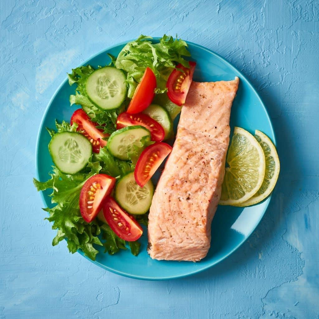 saumon et salade dans une assiette bleue