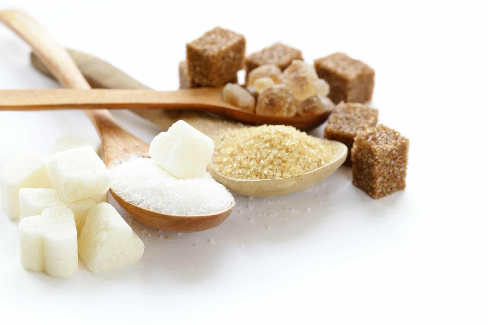 sucre blanc et brun dans des cuillères en bois