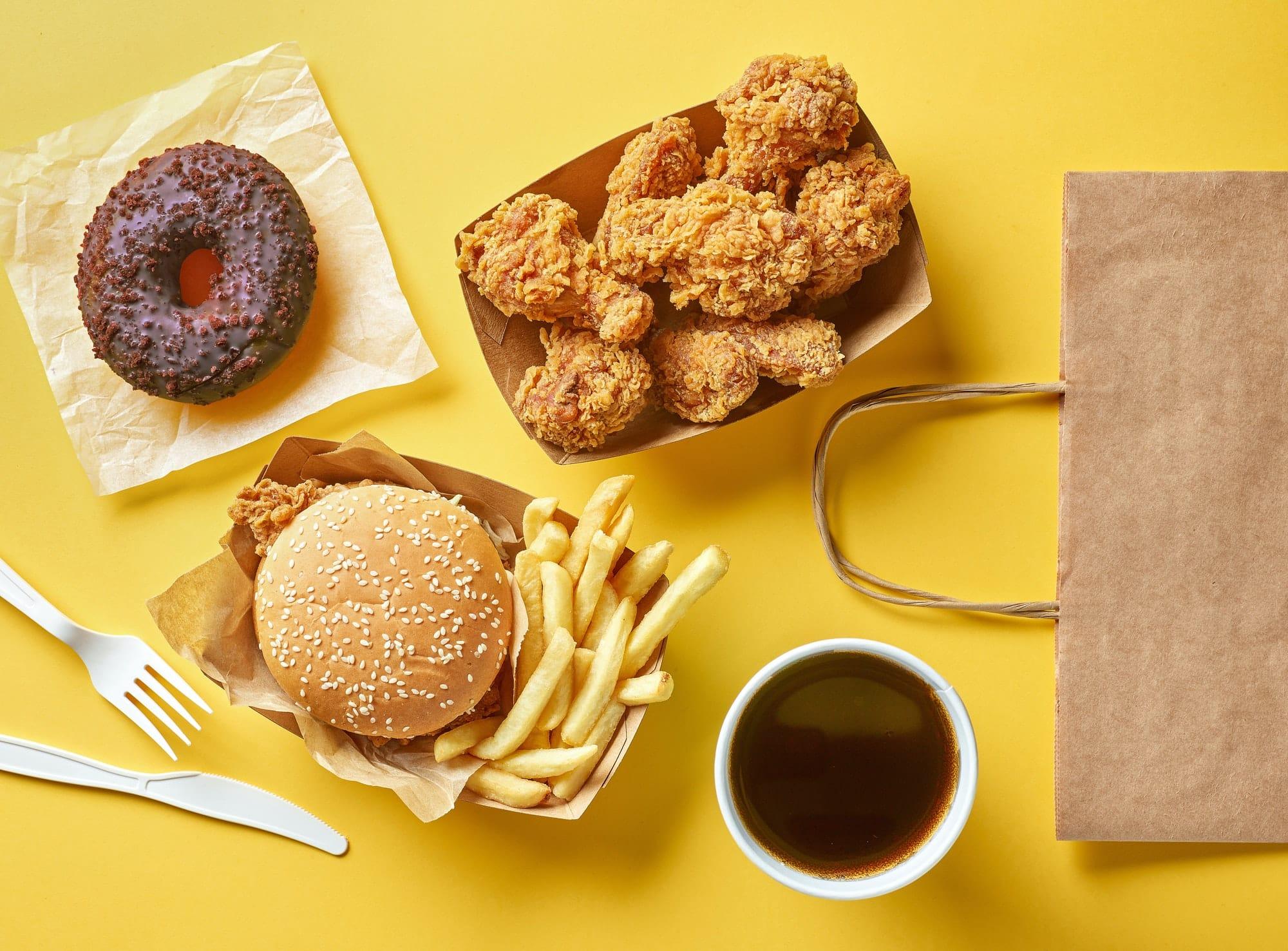 burger donut frites nuggets et café sur fond jaune