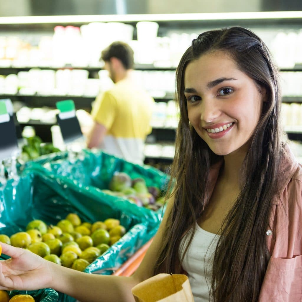 femme achète des fruits frais dans un magasin paléo